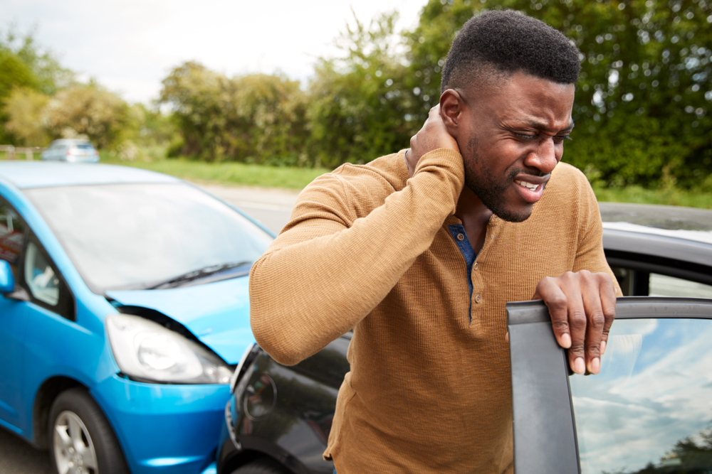 Man holding his injured neck after car wreck