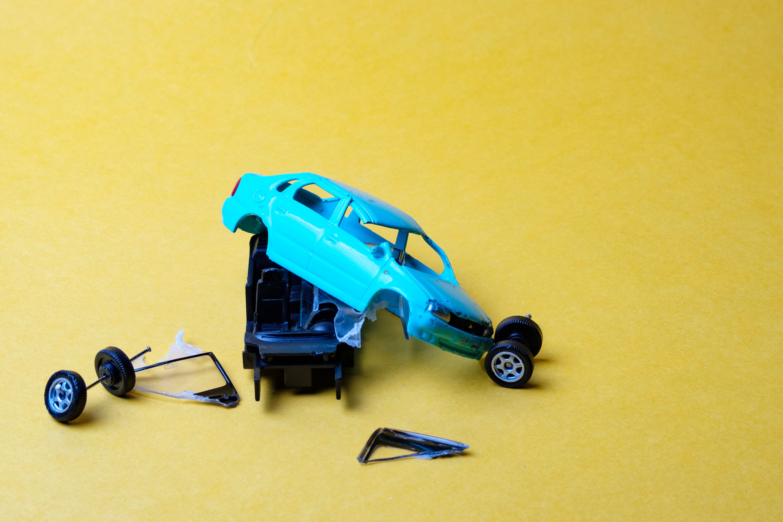 toy car broken into pieces, wheels and glass fell off, yellow background