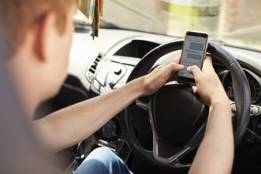 Young Man Sending Text Message Whilst Driving