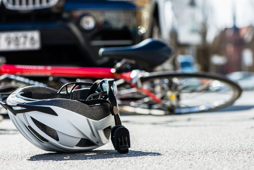Close-up of a bicycling helmet fallen on the asphalt  next to a bicycle after car accident on the street in the city
