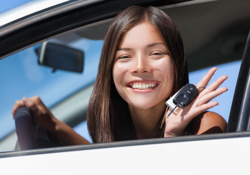 Happy Asian girl teen driver showing new car keys. Young woman smiling driving new car holding key. Interracial ethnic woman driver holding car keys driving rental car.